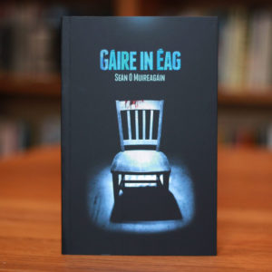 Cover of book Gáire in Éag depicting a bloodied chair under a harsh spotlight.